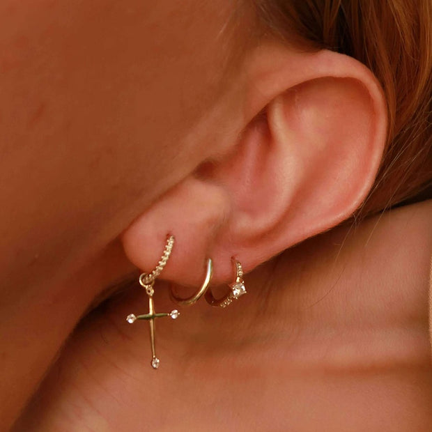 woman wearing 14K gold plated sterling silver huggie hoop cross zirconia drop earrings