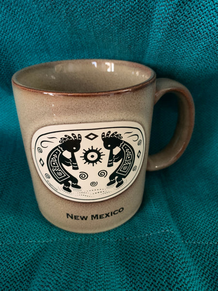 Two kokopelli on side of mug with New Mexico written on.