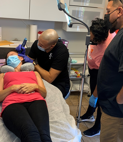 Recording crew is rolling as Seif Sidky, during a scalp micropigmentation procedure on a woman