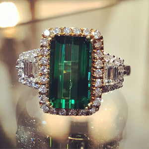 Vivid 2.54 carat emerald cut green tourmaline. 0.74 carats of round brilliant cut and trapezoid diamonds on 18k white and yellow gold
