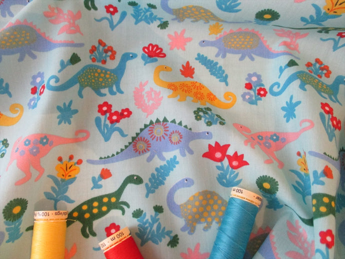 Dinosaurs on a Sky Blue Background Poly Cotton
