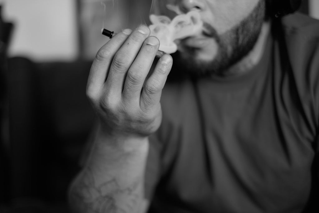 Bearded man exhales smoke after taking a hit from a cannabis joint