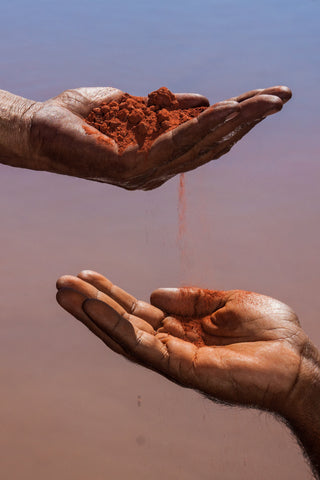 Aboriginal Australians exchanging red soil from hand to hand