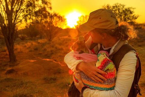 Conservancy worker cradling a young baby kangaroo in a knitted pouch