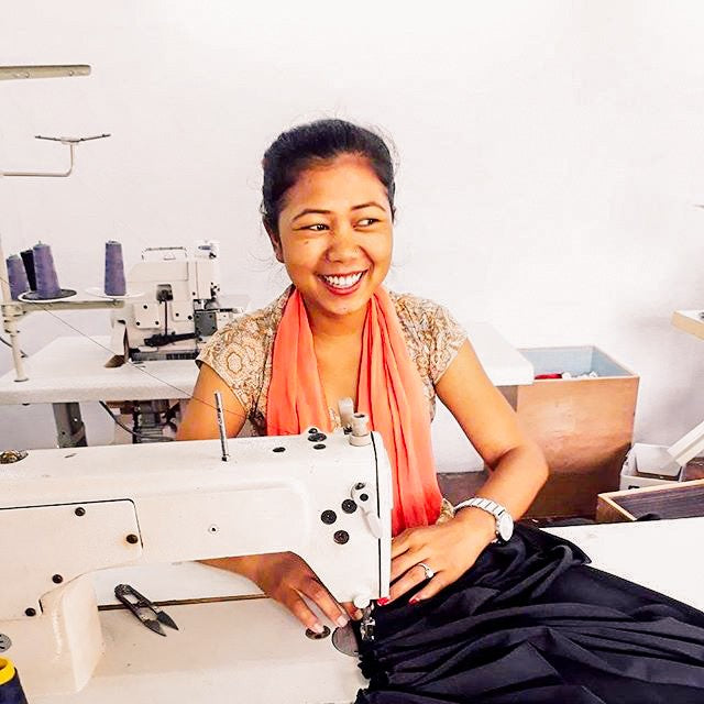 artisan smiling at sewing machine