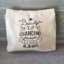 "Load image into Gallery viewer, ""Beauty is Changing Lives in Haiti"" Cotton Canvas Reusable Shopping Tote Bag"