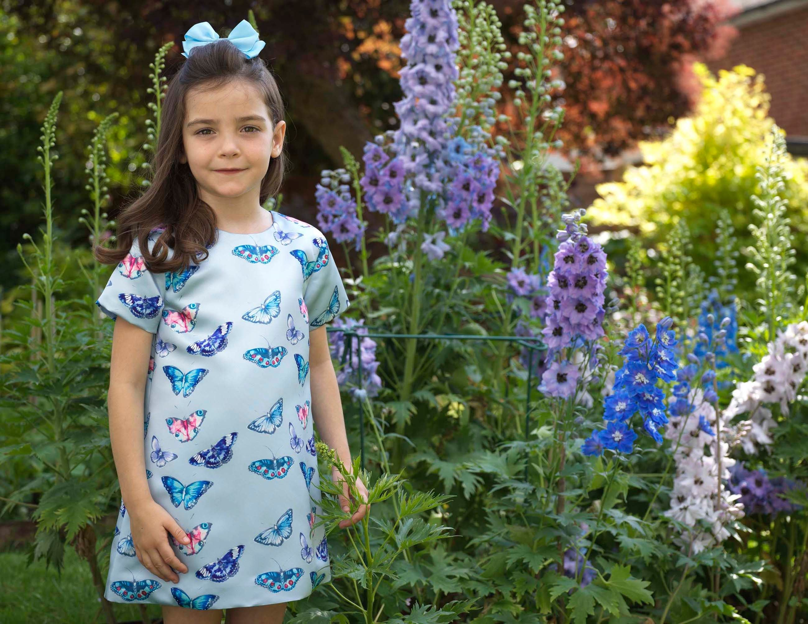 Young girl in butterfly print satin dress in floral garden