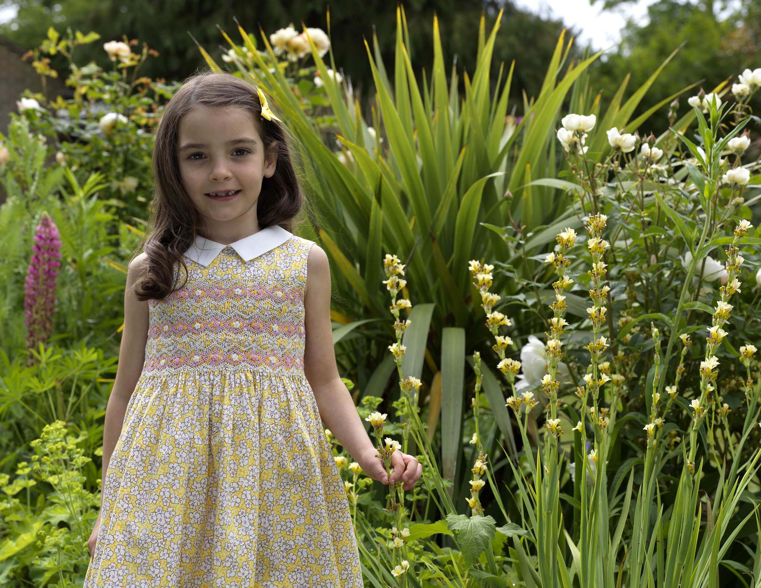 Young girl in yellow floral dress standing in floral garden