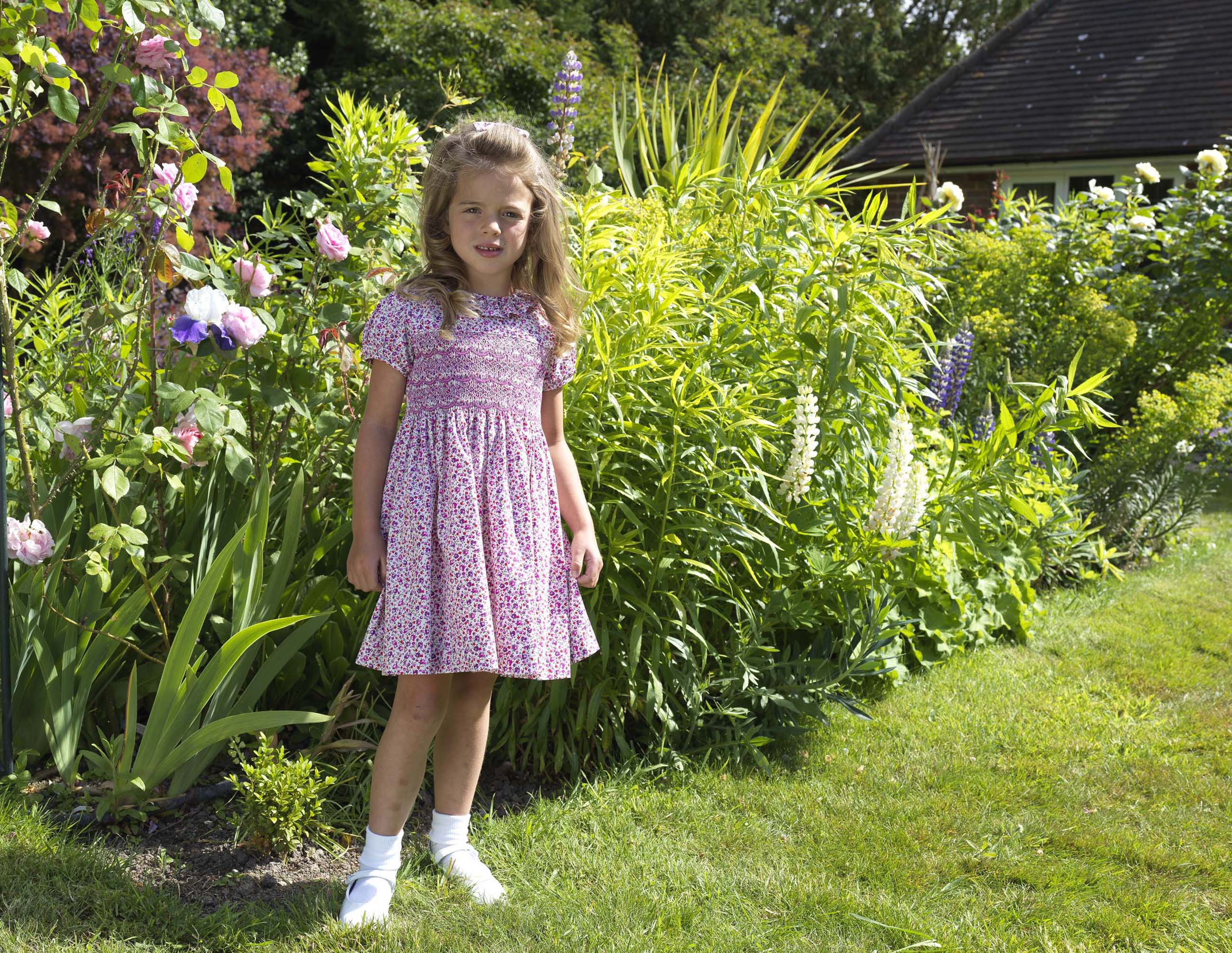 Young girl in pink floral dress in floral garden