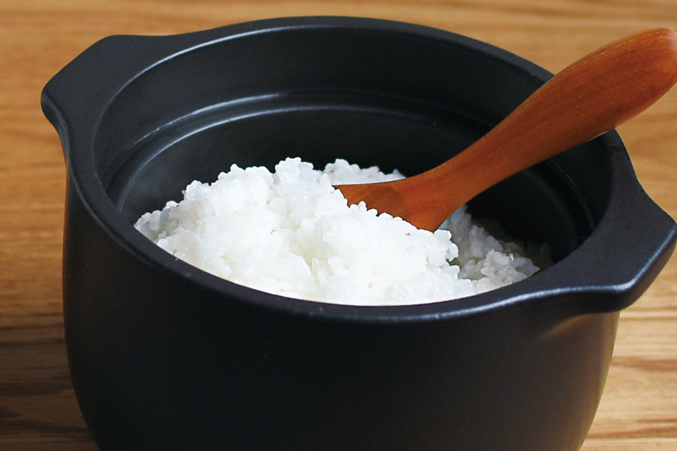 KAKOMI rice cooker with rice and wooden spoon