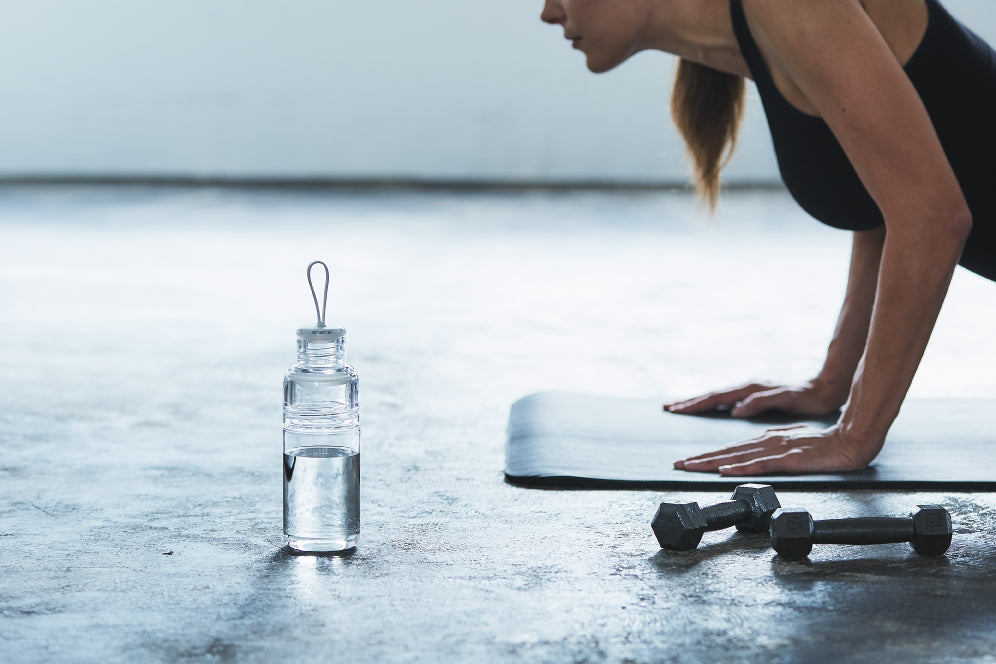 Exercising next to WORKOUT bottle clear