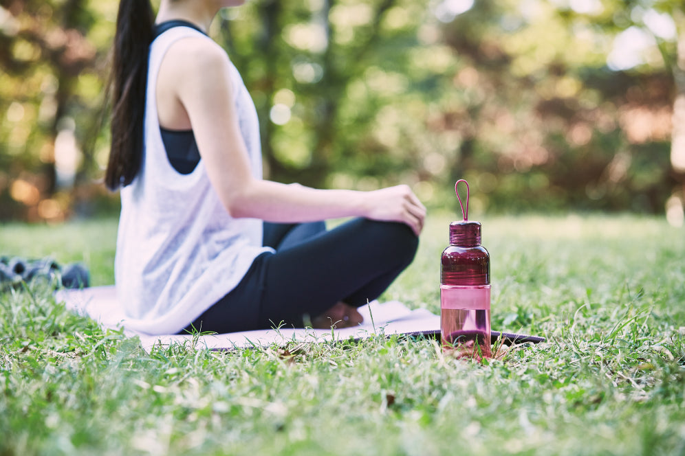 Magenta WORKOUT bottle next to lady sitting on a yoga mat