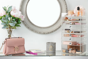 A vanity table set up with a light pink purse and flowers right a makeup organizer tower to the right of it, filled with makeup.