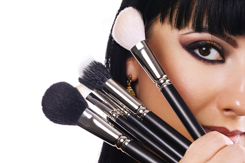 a woman holding up makeup brushes to her face