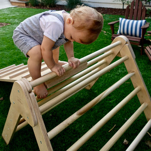 Toddler climbing on the best Pikler Triangle to improve his gross motor skills.  Foldable Pikler Climbers for early childhood development.
