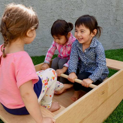 children playing on a handmade montessori wooden rocking boat.  Safe sturdy and wonderful to play on.  Play is the work of the child which is why we offer rocking boats pikler triangles and nursery furniture.  Great for montessori classrooms.w