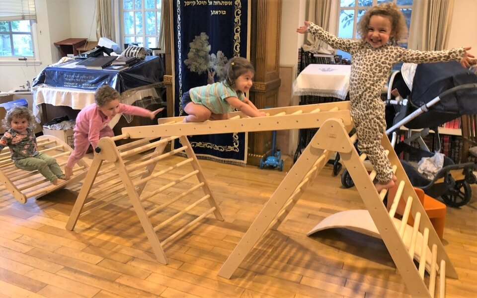a whole family enjoying two pikler triangles connected with ladders and ramps