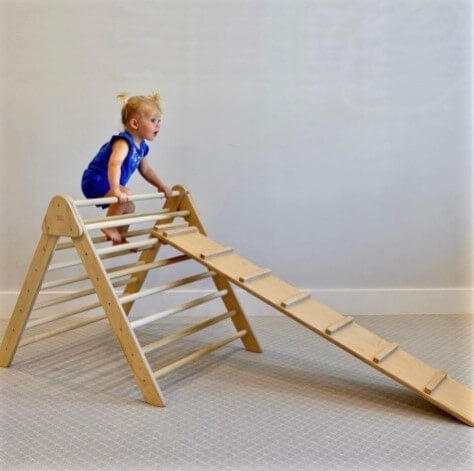 Child climbing on handmade pikler triangle.  Sometimes called a pickler triangle this safe and non toxic wooden montessori climber is a bestselling item from our gross motor development furniture including rainbow rockers, boats and large pickler triangle