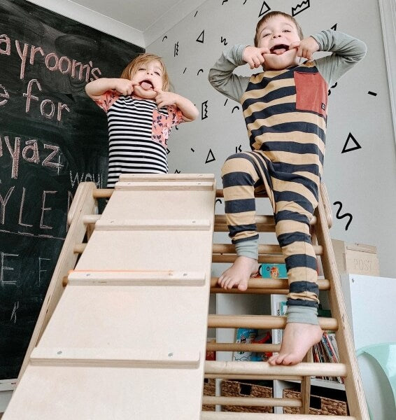 two kids playing around on top of best pikler triangle made in USA