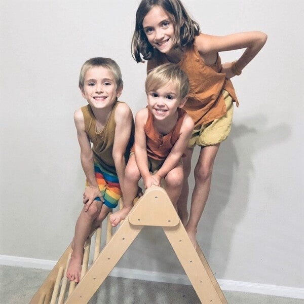 family of three kids on top of american made montessori climber
