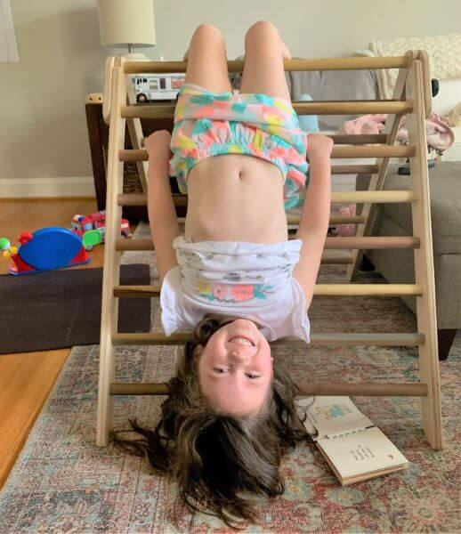 kid hanging upside down from pikler triangle