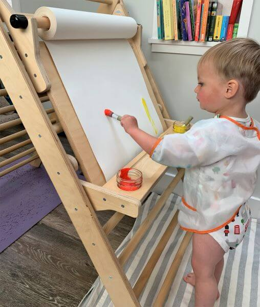 toddler painting at childrens easel attached to pikler triangle