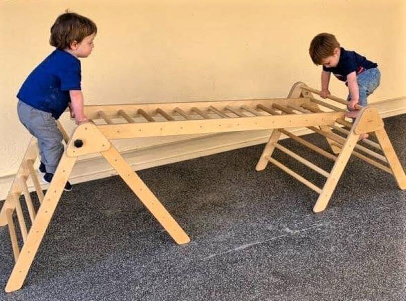 two kids climbing pikler triangles with ladder attaching them