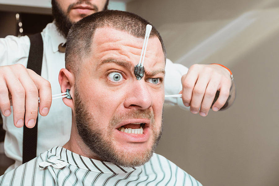 Surprised man getting his face and ears waxed