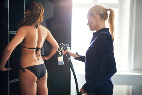 image of a woman having a professional spray tan done