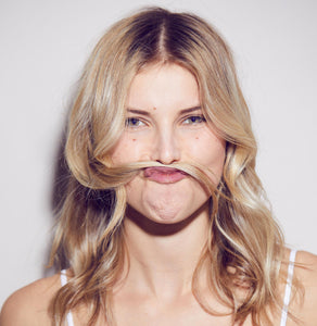 A woman posing with her long hair as a fake moustache