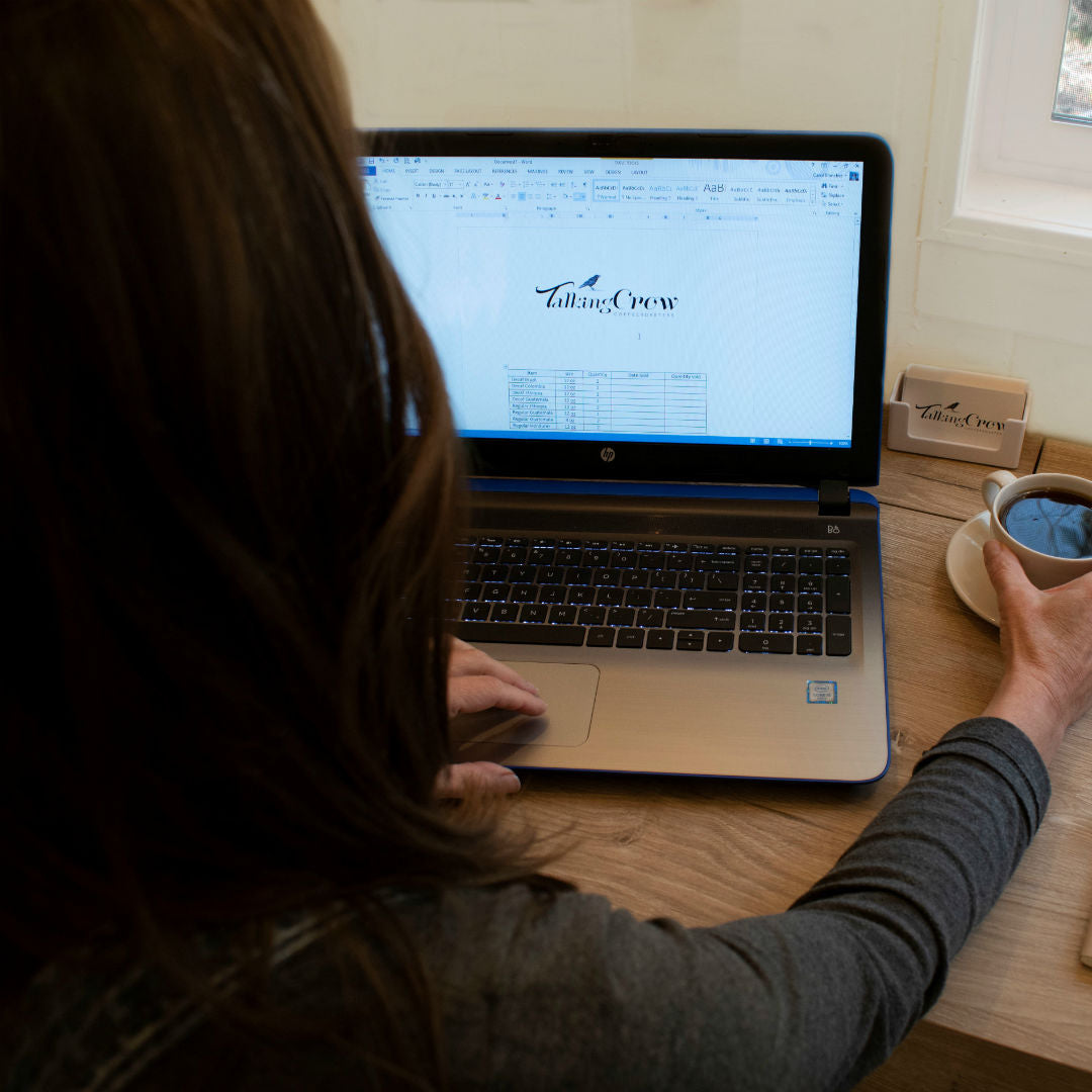 Image of a person sitting in front of a laptop with a cup of coffee