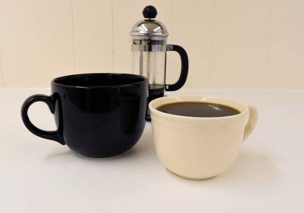 Image of two full coffee mugs one black and one white regular and decaf black coffee