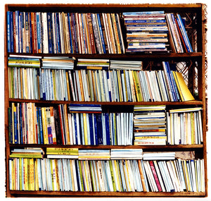 Multi-color books in a book case square photograph