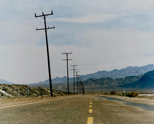 An open road in Amboy, California, featuring telephone poles disappearing into the mountainous distance. This classic and timeless landscape photograph is part of Richard Heeps' 'Dream in Colour' series.