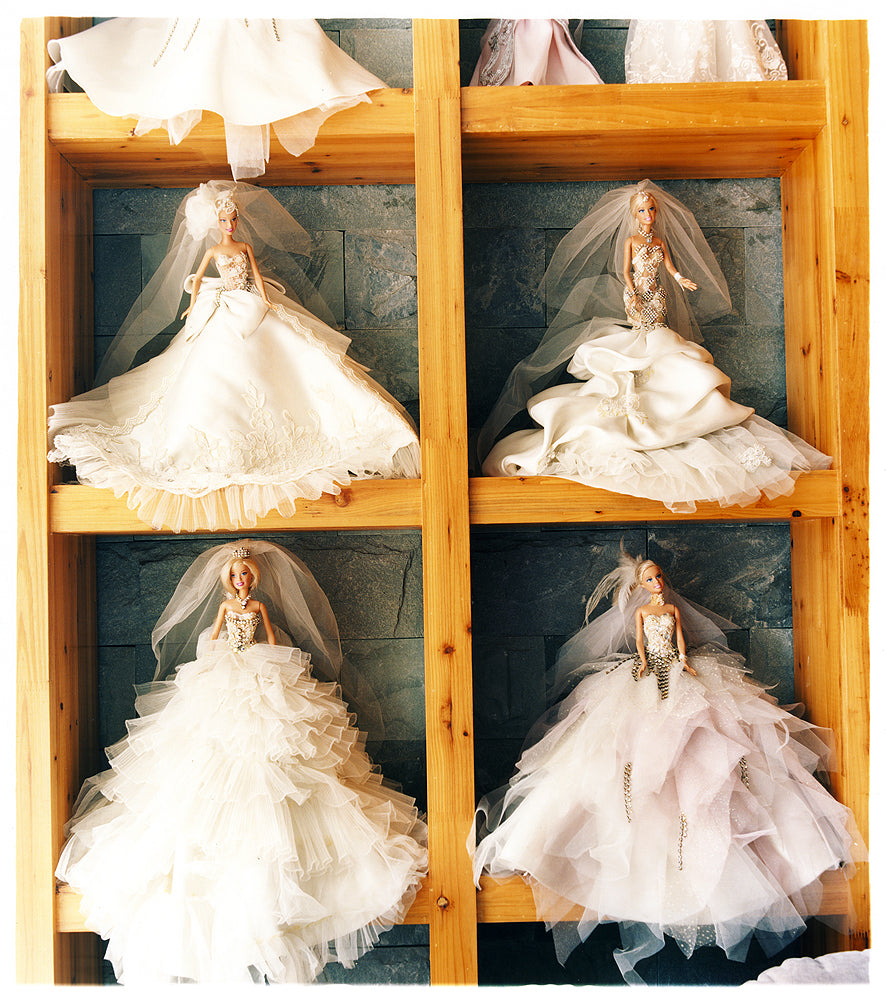 Four Barbie dolls in wedding dressed on a shelf.