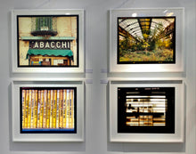 Load image into Gallery viewer, As part of Richard Heeps' series, A Short History of Milan, Delitto A Hollywood features a series of yellow Italian books from a street kiosk.