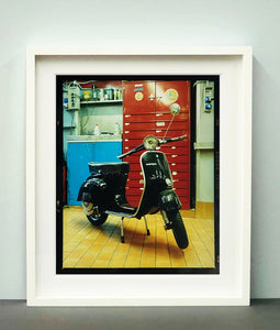 A black vespa against a red, blue and yellow interior. Photographed in Milan, Italy.