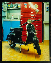 Load image into Gallery viewer, A black vespa against a red, blue and yellow interior. Photographed in Milan, Italy.