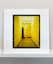 Load image into Gallery viewer, A yellow glow fills the corridor of an apartment foyer in Milan.