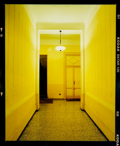A yellow glow fills the corridor of an apartment foyer in Milan.