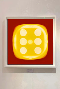 From Heidler & Heeps Dice Series, a yellow dice suspended on a red background.