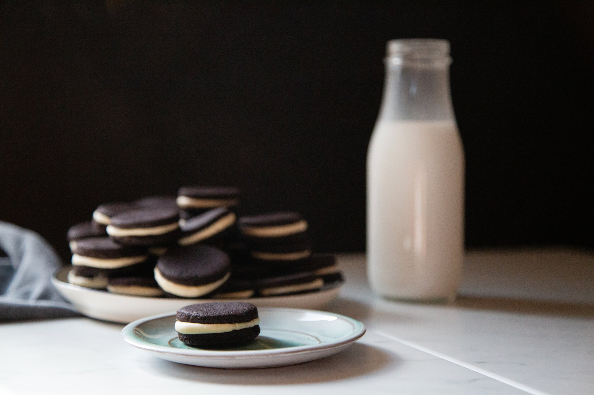 homemade oreo cookies with jar of milk on the side made using black velvet cacao powder by weirdo good