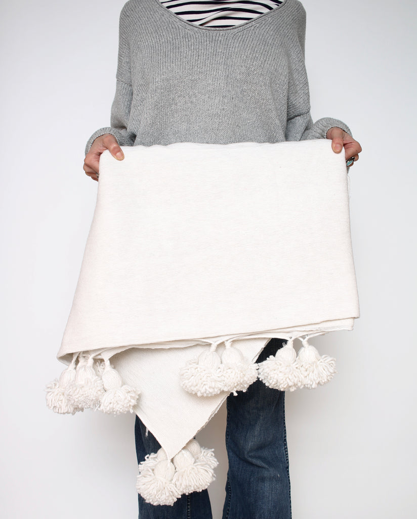 model holding white pom pom blanket
