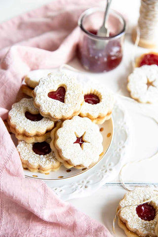 Linzer cookies are a combination of buttery orange infused shortbread and jam, as pleasing to look at as they are to eat