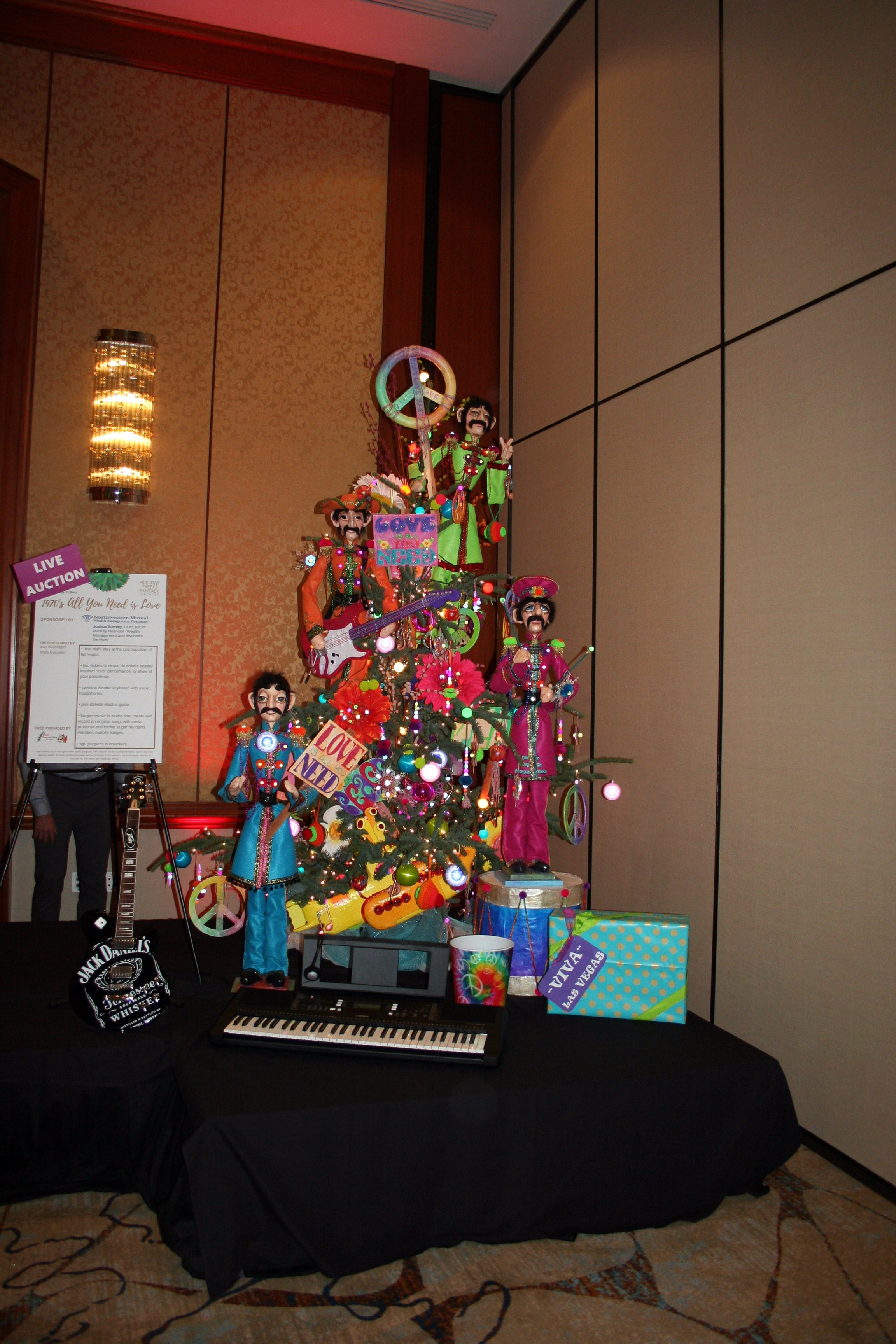 A 70's themed Christmas tree decorated with dolls and musical item, next to a sign labeled as live auction item