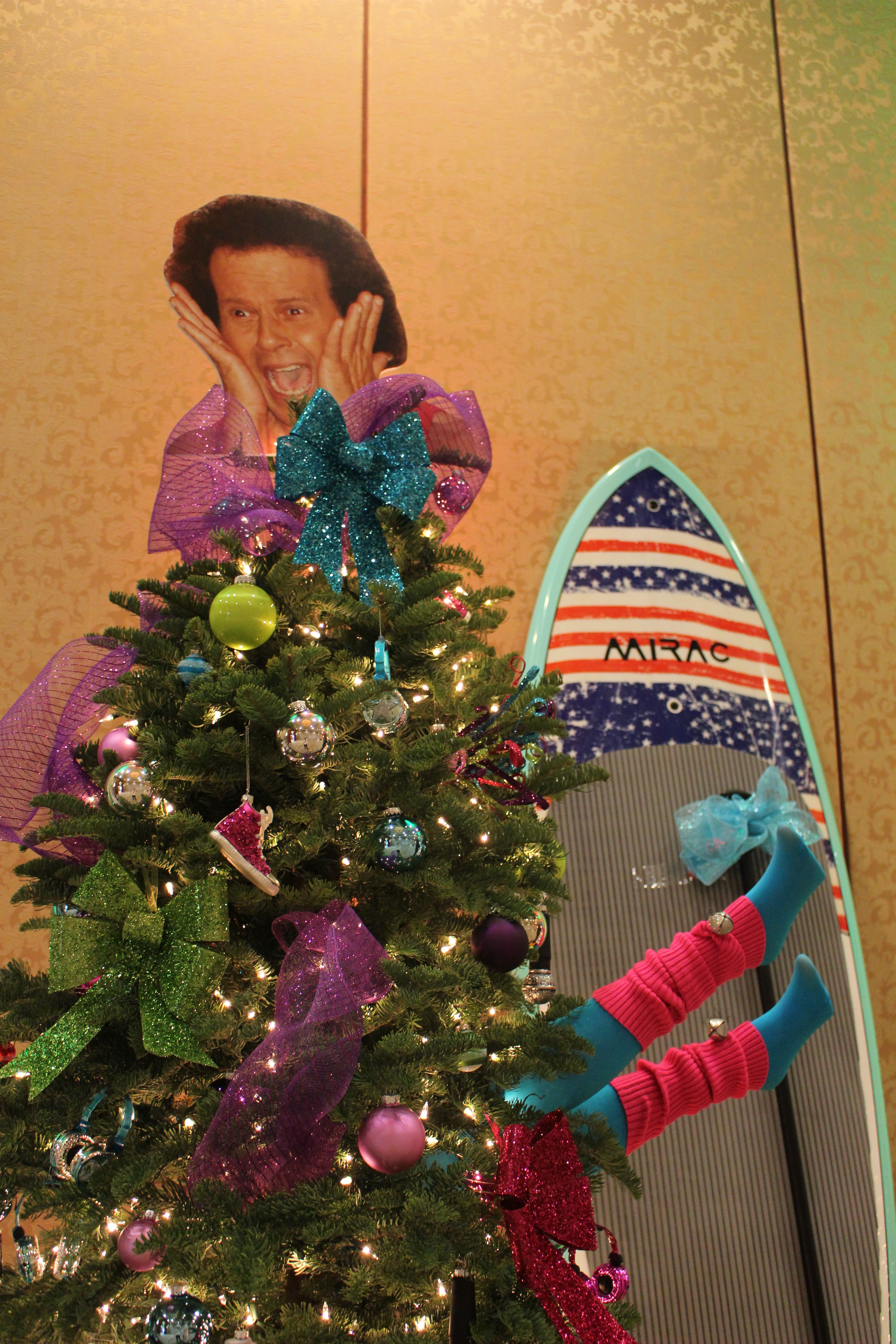 An 80s-themed Christmas tree topped with a big head cardboard next to a surfboard