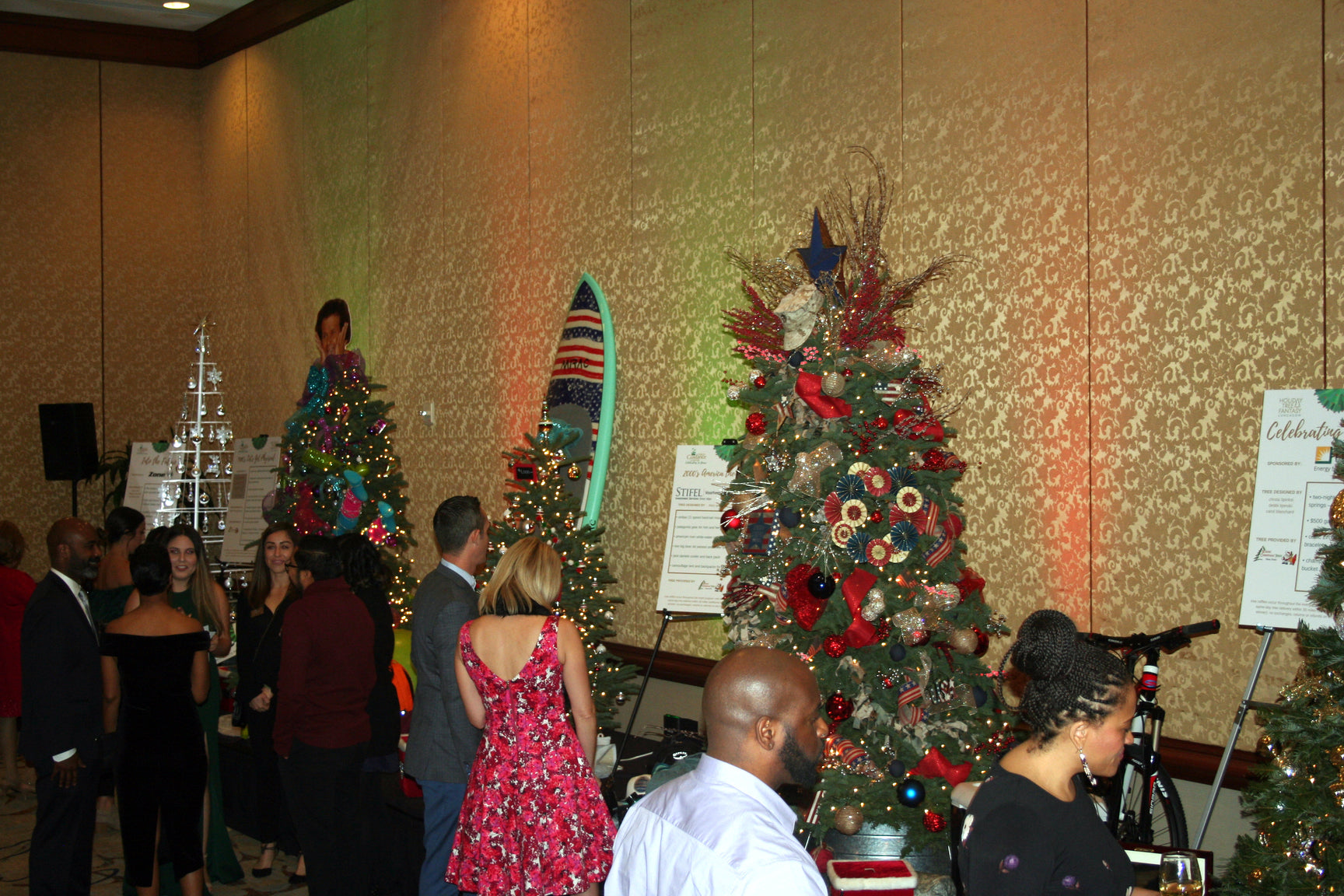 A crowd looking at items displayed and decorated Christmas trees