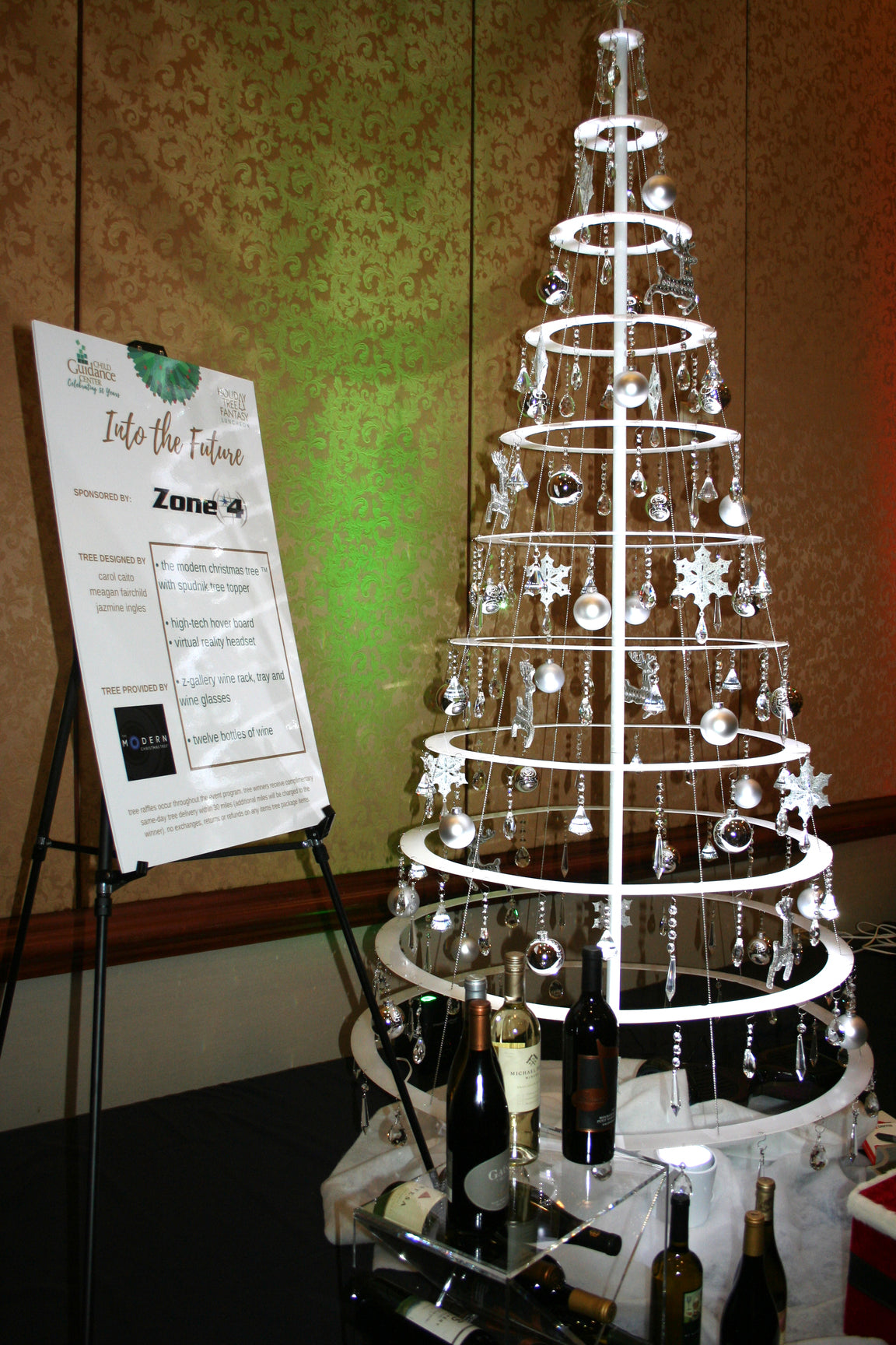 A wired Christmas tree in white decorated by various ornaments placed next to wine bottles and an information board