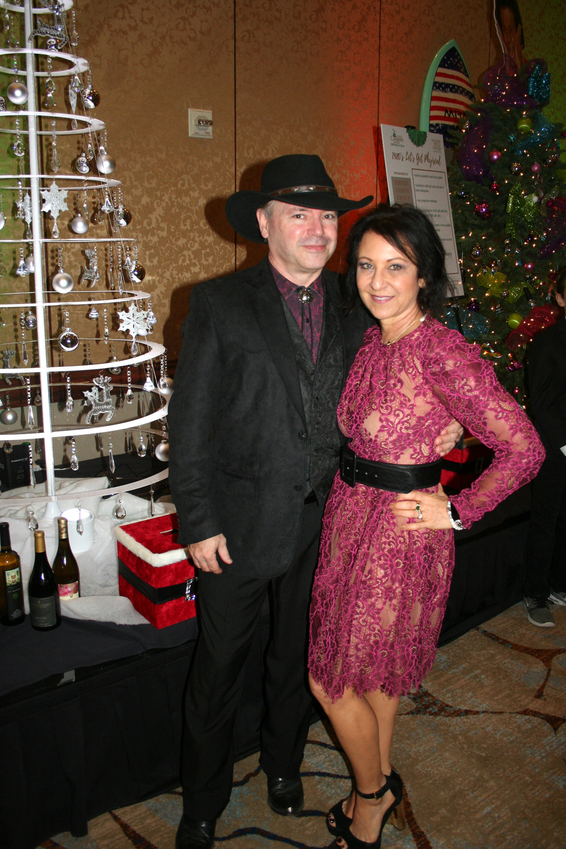 A man and a woman posing next to a wired Christmas tree in white