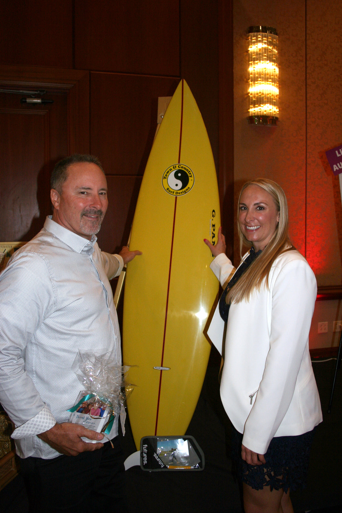A man and a woman posing in front of a surfboard